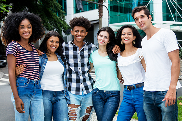 Group of young people with their arms around each other
