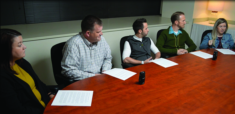 Image of people sitting around a conference table