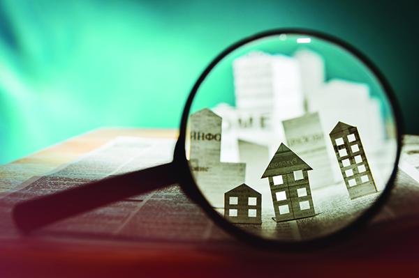 Image of a magnifying glass showing small buildings cut out of paper