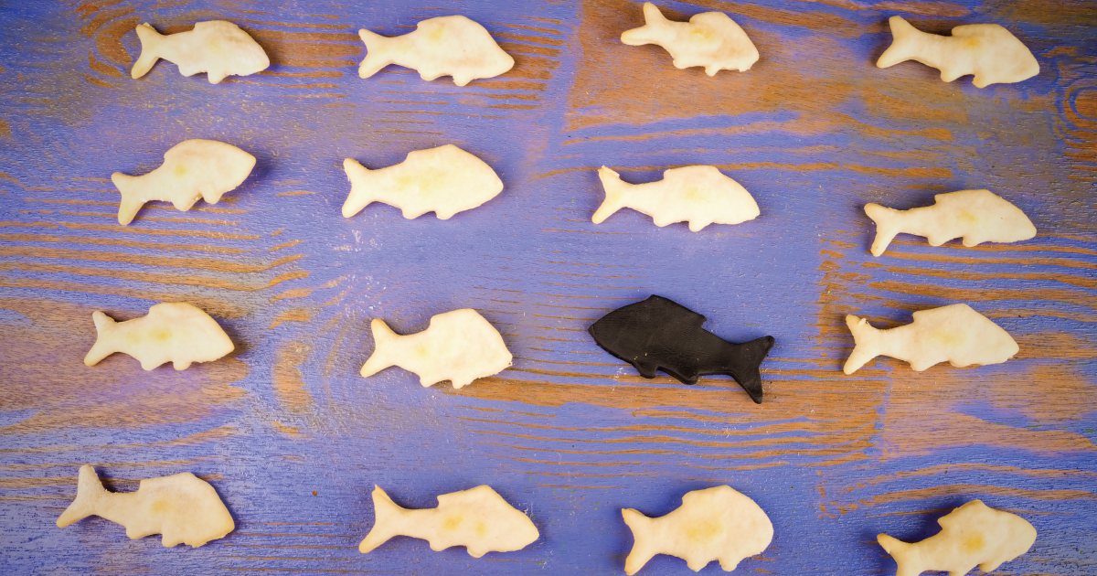 A field of white crackers shaped like fish facing one way, with one black fish facing the other way