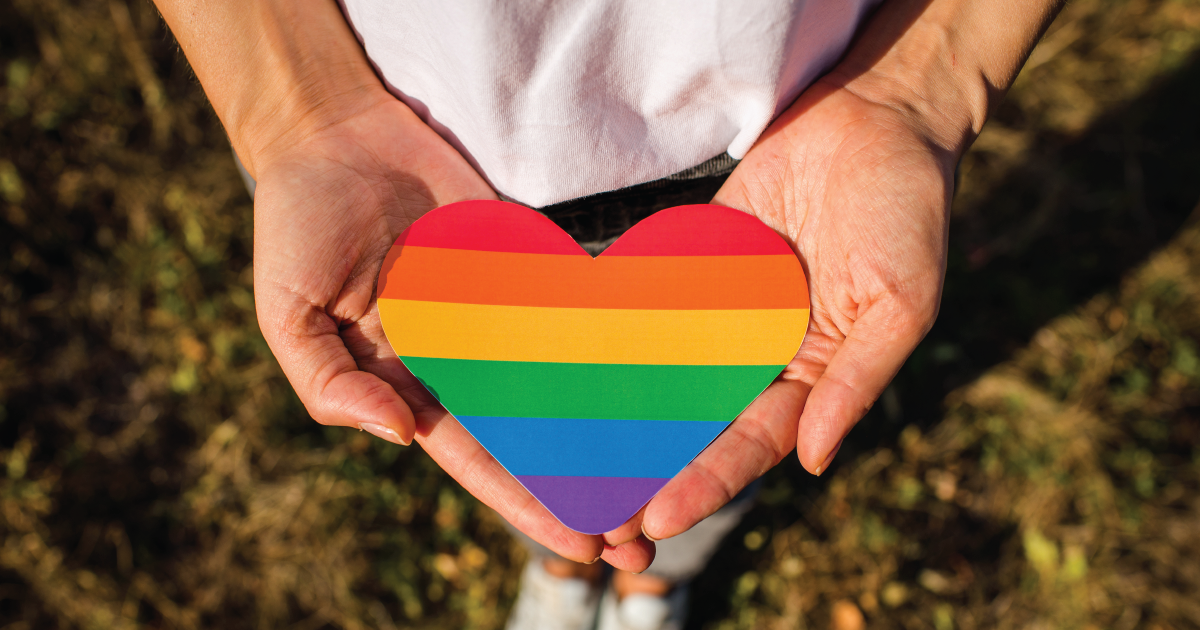 Person holding a heart that is painted in the colors of the rainbow flag