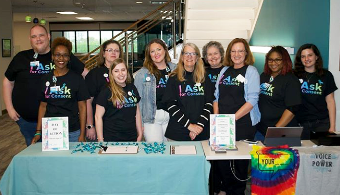 A group of individuals stand in front of their SAAM table at their Day of Action event.