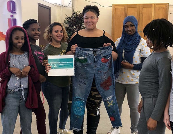 A group of young girls hold up a pair of decorated jeans.