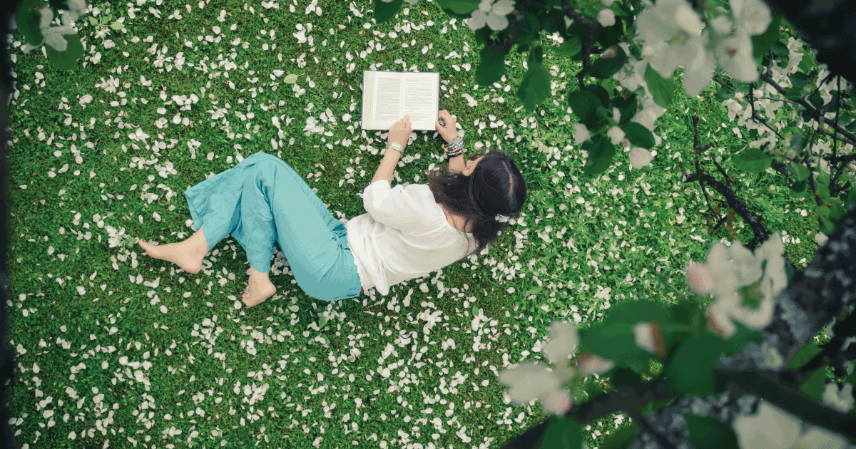 Young woman lying down on the grass outside reading, surrounded by flowers petals