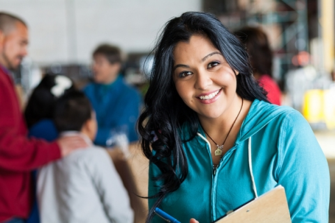 Woman smiling wearing a teal hoodie and holding a clipboard