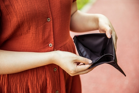 Woman looking in empty wallet