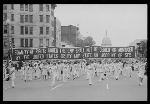"Women wearing all white marching in the street and carrying a banner that says ""Equality of rights under the law shall not be denied or abridged by the United States or by any state on account of sex"""