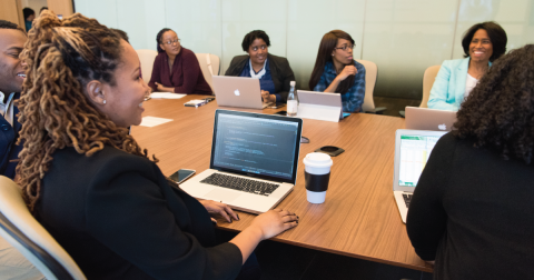 A team of people of color sitting around a conference table with laptops