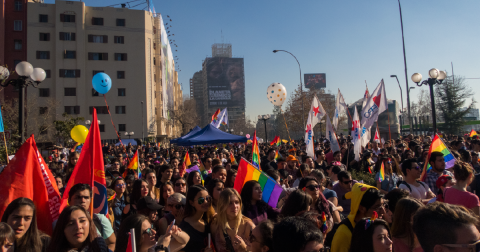 Crowd of people holding rainbow flags in Chile