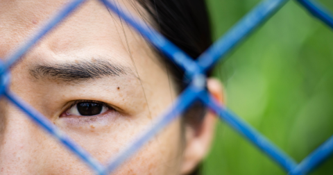 Woman looking through a chain-link fence