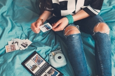 Girl looking through photographs on her bed