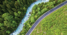 Aerial shot of a winding river next to a road